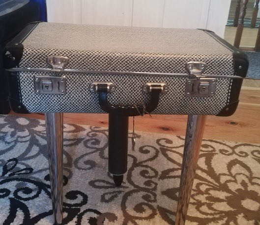 table with two chrome and one wooden leg, made from a black-and-white, vintage suitcase