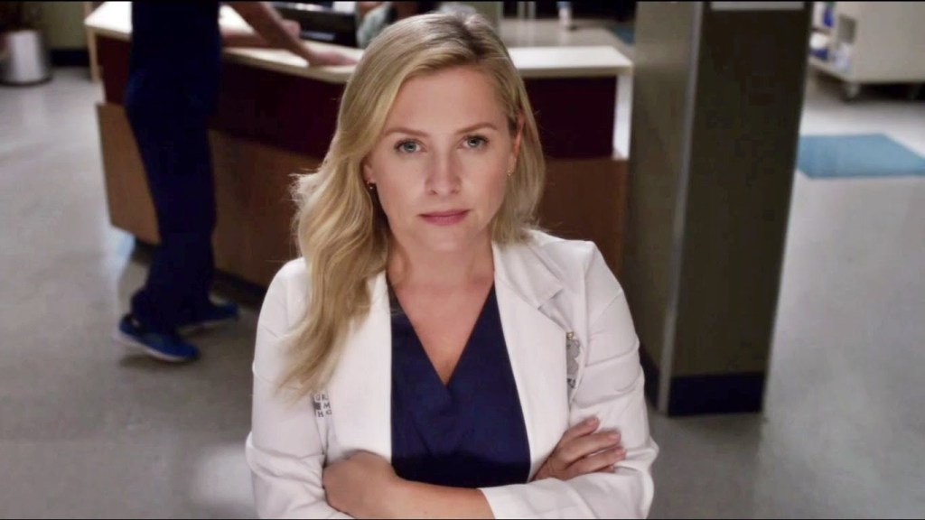 Actress Jessica Capshaw, daughter of Kate Capshaw. Blond, wearing scrubs and white lab coat.