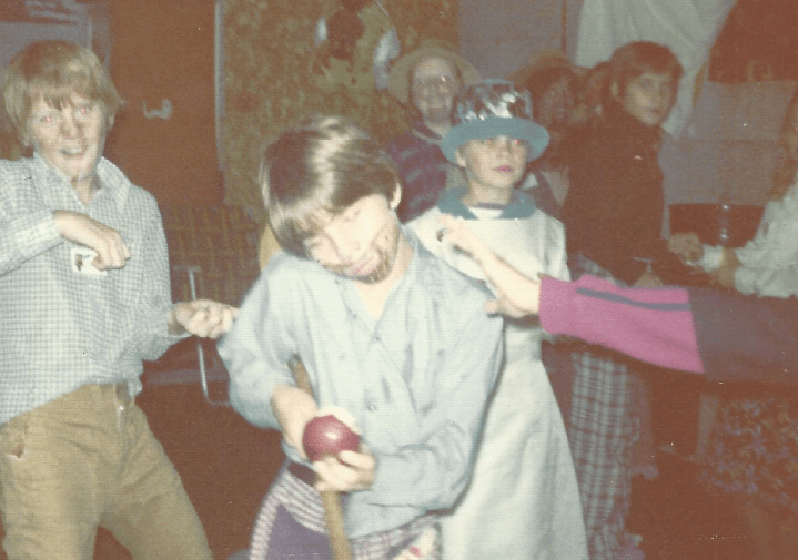 Kids dancing and having fun in costume. One in the foreground is eating an apple he just bobbed for.
