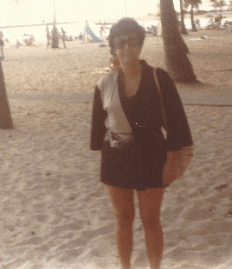 Mom on a beach, thin, in a bathing suit cover-up with huge sunglasses and a towel over her shoulder.