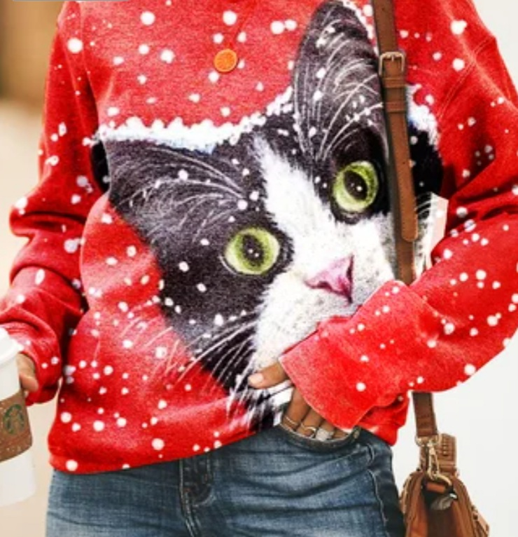 The torso of a woman wearing a bright red sweater with a huge cat face covering almost the entire front of it.