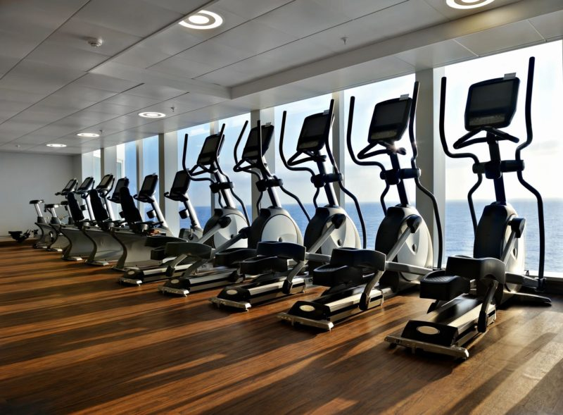 A row of treadmills on a hardwood floor in front of floor to ceiling windows
