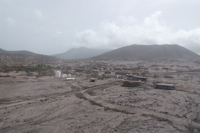 The ghost town of Plymouth, Montserrat, abandoned in 1997 and destroyed by a long series of pyroclastic flows from the Sofrière Hills volcano, visible in the far background (WikiMedia)