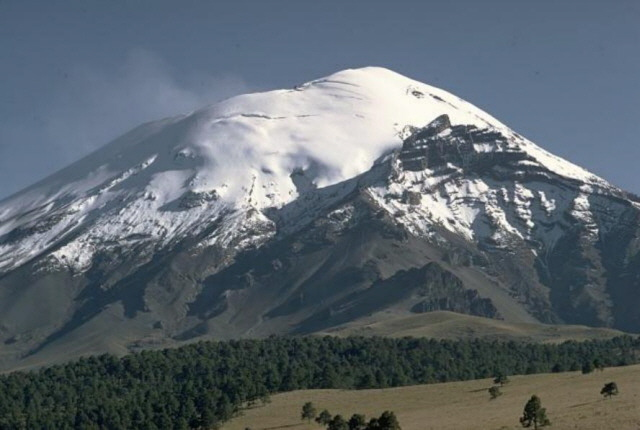 The once glacier-covered peak of Popocatépetl stratovolcano rises above Tlamacas to its north in this photograph from 1968. The sharp peak at right is Ventorrillo, the summit of a predecessor to Popocatépetl, the eroded Nexpayantla volcano. (William Melson)