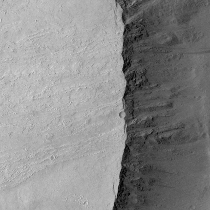 Fig 6. Mars HRISE high-resolution image of the escarpment just to the south of the area of exploration with the upper slopes of Olympus Mons to the left. This image gives an idea of the terrain encountered by the rovers. The lack of heavy cratering is thought by some to be indicative of volcanic activity as late as 200 – 2 million years BP but could equally well be explained by the effects of erosion and landslides over the past 3.5 GY (billions of years). Once you start looking at the image, scores of heavily eroded craters become apparent. Scale of the image was not available. (NASA/ESA)