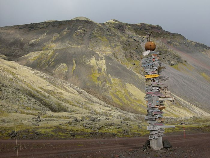 Photographer: Hannes Grobe, released under GNU. A desolate sign-poste with a cinder cone in the background. Jan Mayen, the northernmost active volcano.