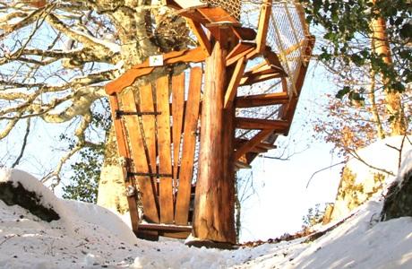 Cabane perchée dans les arbres Cantal Auvergne chemin enneigé