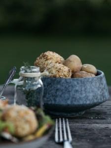 Käse-Blumenkohl Bällchen und Kartoffeln in einer grauen Schüssel auf einem Holztisch