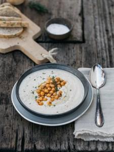 Blumenkohl Suppe mit gerösteten Kichererbsen und frischen Kräutern. Auf dem Holzuntergrund liegt ein weißes Tuch. Die Suppe ist in einer schwarzen Schüssel die auf einem weißen Teller steht. Brot liegt neben dem Bild.