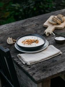 Blumenkohl Suppe mit gerösteten Kichererbsen und frischen Kräutern. Auf dem Holzuntergrund liegt ein weißes Tuch. Die Suppe ist in einer schwarzen Schüssel die auf einem weißen Teller steht. Brot liegt neben dem Bild. Der Tisch ist sichtbar. Ebenso ein Stuhl. Im Hintergrund ist der Garten sichtbar. Es handelt isch um ein Winter-Gathering.