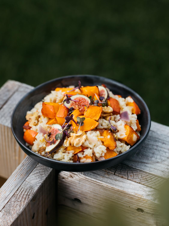 Kürbis-Chèvre Risotto mit Walnusskernen & Feigen. Dieses Bild zeigt das Gericht in einer Bowl angerichtet und servierfertig auf einer Holzpalette.