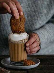 Glas mit Kaffee und Milchschaum. Das glas steht auf einem Teller. Davor liegt ein Cookie. Es wird in der Hand gehalten. Die Person trägt eineng rauen Wollpullover.