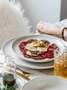 Karamellisierter Ziegenkäse auf Rote Beete Carpaccio, serviert auf einem weißen Teller.