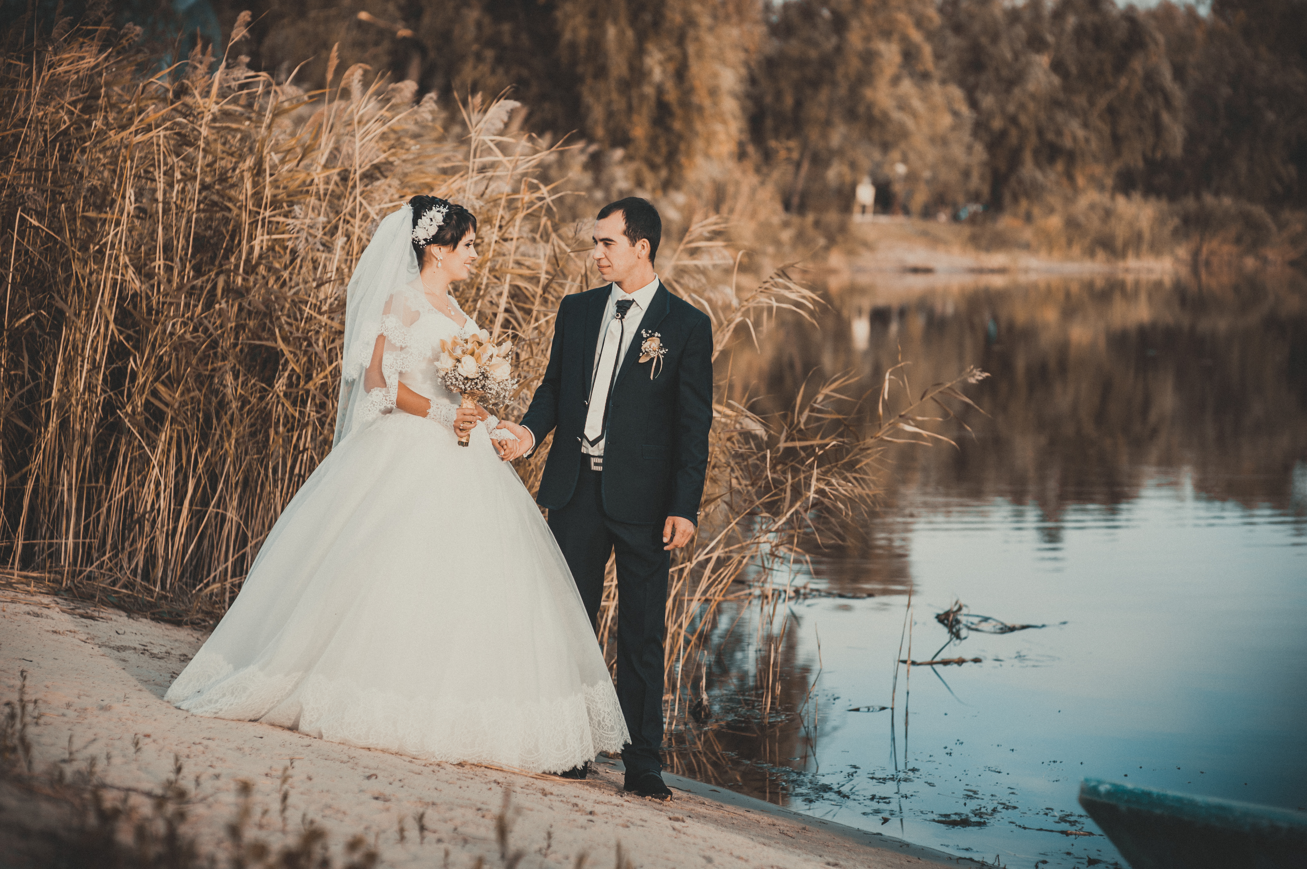 wedding: bride and groom on the seashore. Honeymoon. The bride and groom hugging on the shore of Lake. groom and bride hugging on a green lake. Groom and Bride in a park. wedding dress. Bridal wedding bouquet of flowers