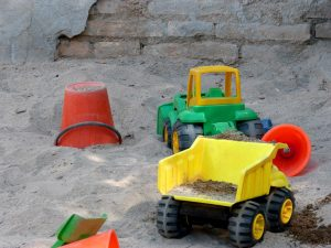 toy trucks and bucket in sandbox as a metaphor for playing with volunteerism
