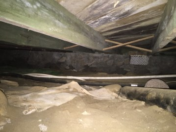Photo ofCrawl Space with missing vapor barrier on dirt floor and mold growth on joists and sub flooring.