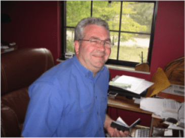 Photo of Bob Byrne Volunteer Inspections, Knoxville, TN sitting at his office desk.