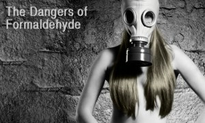Photo of a nearly naked woman with a chemical gas mask on with long hair covering her breasts