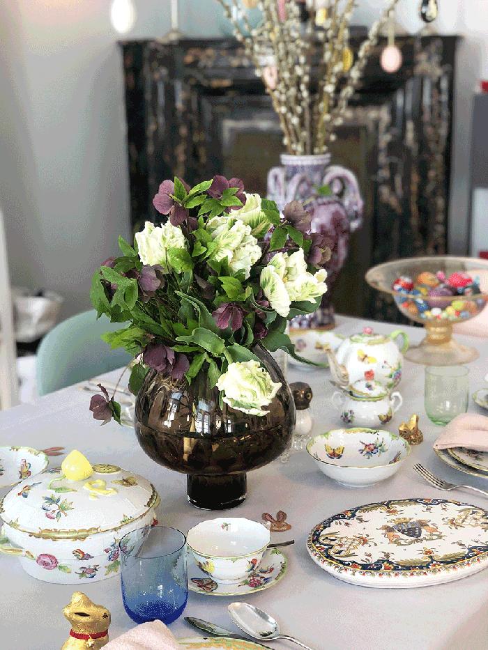 VONsociety: Ostern 2020, Ostertisch von Caroline van Kelst, mit Blumenstrauß in violett und weiß, Porzellan von Herend, einer Schale mit bunten Ostereiern, im Hintergrund Palmenzweige mit bunt bemalten Ostereiern