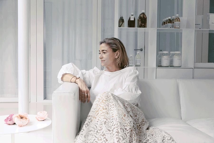 VONsociety: Susanne Kaufmann sitzt auf einem weißen Ledersofa, den Arm auf die Lehne gestützt. Sie trägt einen weißen Rock aus Spitze und eine weiße Bluse mit gebauschten Ärmeln. Der Blick ist nach links gerichtet. Im Hintergrund ein Regal mit Produkten aus der Susanne Kaufmann Naturkosmetiklinie.