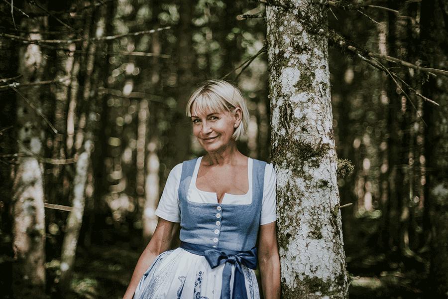 VONsociety: Bettina Grieshofer im eigenen Dirndl mit hellblauem Oberteil und hellblau-weiß gemustertem Rock und Schürze sowie einer einfachen weißen Bluse
