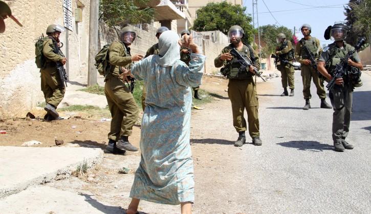A Palestinian woman hurls stone at Israeli soldiers, near Nablus, West Bank, 31 August 2012. EPA/ALAA BADARNEH