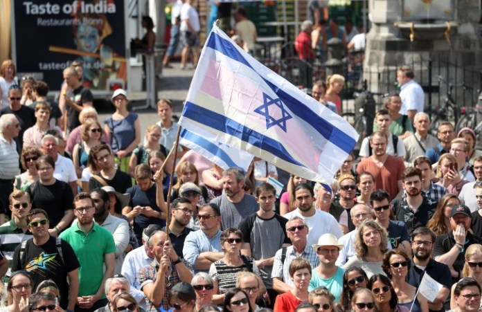 People wave Israeli flags during the kippah day at the market square in front of the historic town hall in Bonn, Germany, 19 July 2018. After the attack and the subsequent police violence against a Jewish professor, the city of Bonn wants to set a sign against anti-Semitism with the Kippah Day.  EPA