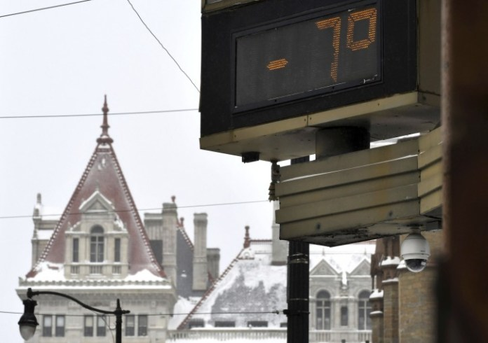 A temperature of -7 degrees Fahrenheit was shown at the Bank of America Financial Center on Sate Street, against a backdrop of the New York State Capitol on Monday morning, Jan. 21, 2019, in Albany, N.Y. (Will Waldron/The Albany Times Union via AP)