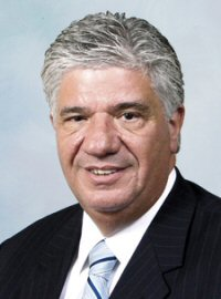 A headshot of Senator Wayne Fontana. He is smiling against a light blue-grey background.