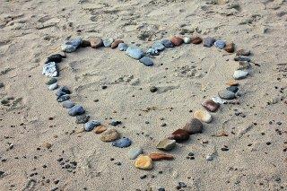 Inventer l'amour. Des cailloux de couleur sont posés sue le sable en forme de cœur.