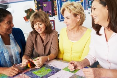 femmes d'âge mûr réunies autour d'une table avec des tissus