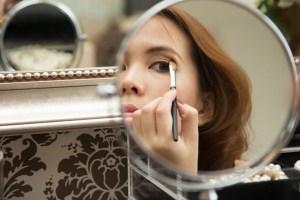 femme qui se maquille dans un miroir rond