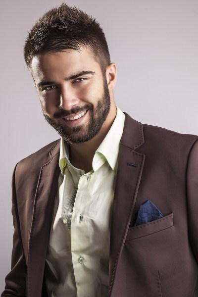 homme barbu avec une veste marron et une chemise vert pâle