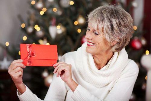 femme d'âge mûr tenant une enveloppe cadeau
