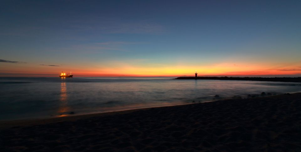 View of the beach and lighthouse from the beach at dusk