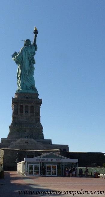 Vue sur l'arrière de la statue de la liberté et l'entrée pour la visite du piédestal.