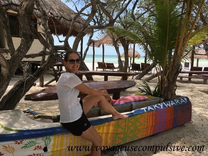 Vue sur une plage typique de l'île d'Holbox, avec palmiers, chaises longues et eau turquoise !