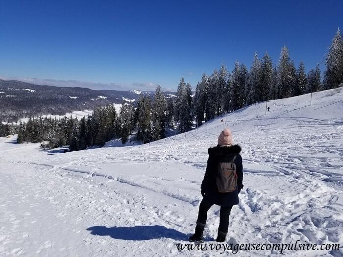 Vue sur les pistes de ski et la vallée enneigé, lors de l'ascension du Montrond dans le Pays de Gex.