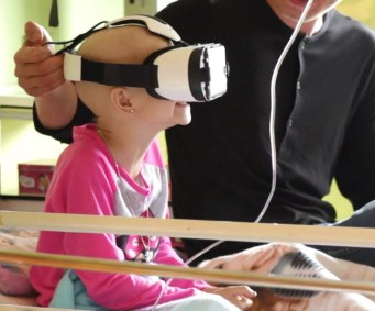 Young girl in hospital bed with VR goggles