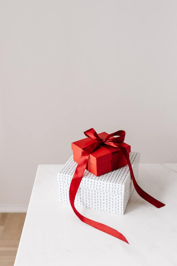 Een stapel kerstcadeaus. duurzame kerstcadeaus. Source: https://www.pexels.com/photo/red-and-white-boxes-placed-on-each-other-on-white-table-4397844/