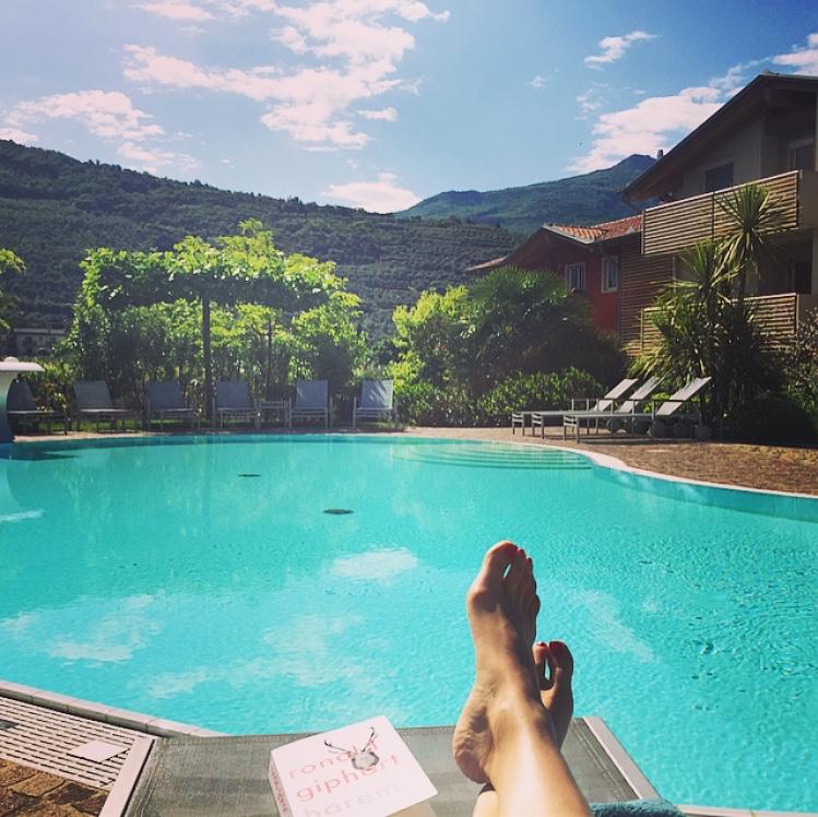 Blote voeten op een ligstoel met een boek aan het zwembad
