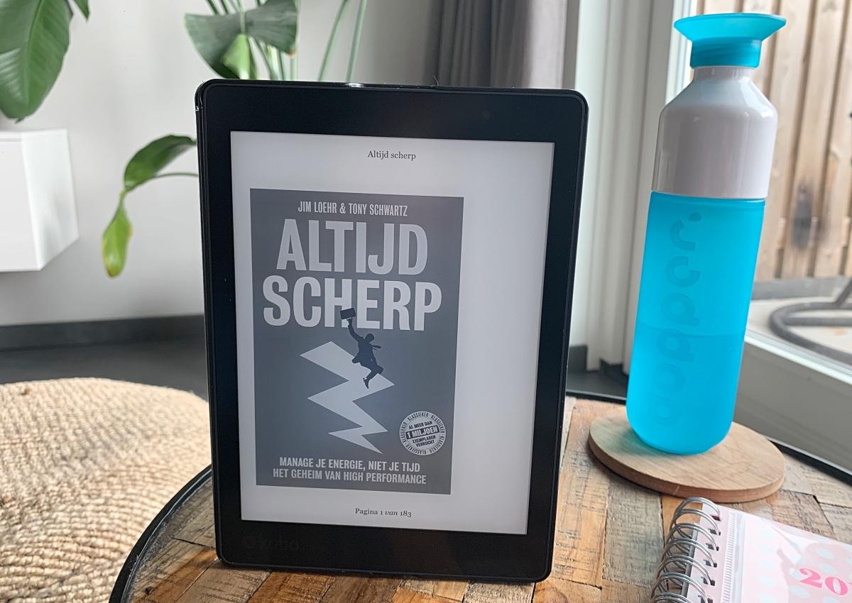 E-reader met daarop het boek Altijd Scherp, Manage je energie, niet je tijd, van Jim Loehr en Tony Schwartz op een tafeltje in de woonkamer met daarnaast een dopper waterfles en een agenda.