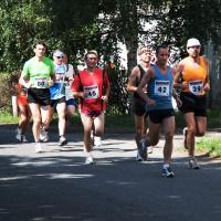 Běžci se blíží k všestudskému obecnímu úřadu.