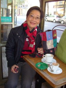 A woman (Trần Thị Thủy Ngọc) seated and smiling in a coffee shop
