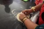 Харониса показывает, как раскатывает тесто для роти