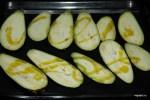 Выкладываем баклажаны на кулинарный коврик и поливаем оливковым маслом