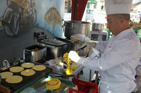 Колумбийский повар жарит  арепас на рынке Пленпале в Женеве
