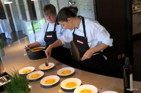 Повара Кулинарного клуба рисуют бальзамическим уксусом на поверхности овощного супа