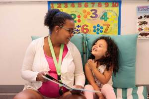 Early childhood educator and child read a book together