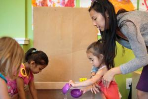 Early childhood educator at water table with children